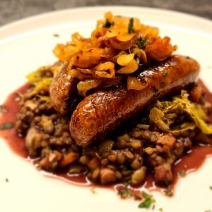 Butchers Sausage over braised lentils and buttered cabbage, with caramlised onions