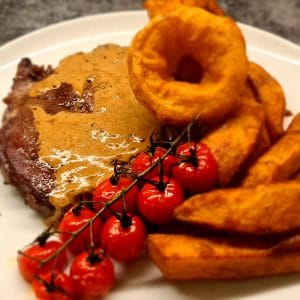 Triple Cooked Chips served with Rib Eye steak, onion rings and tomatoes